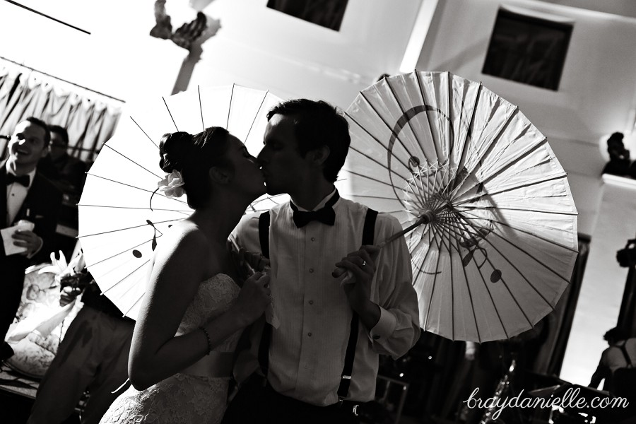 Bride and groom kissing with parasols umbrellas, wedding by Bray Danielle Photography