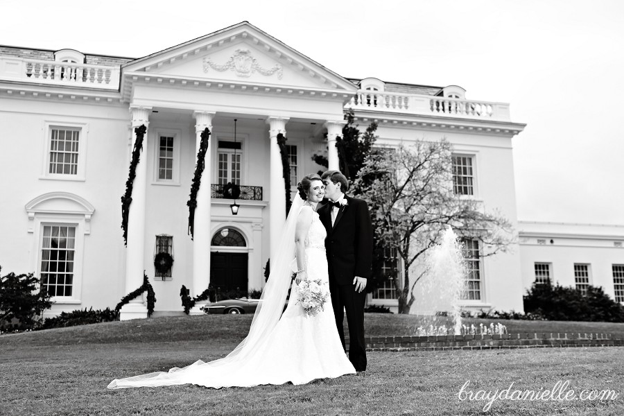 bride and groom in front of mansion
