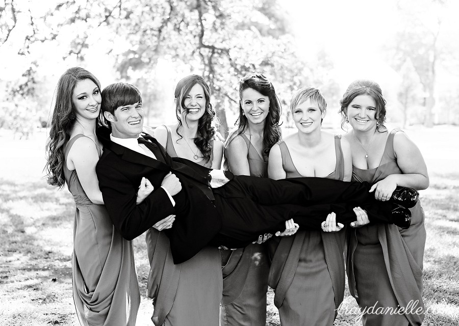 Bridesmaids holding groom up