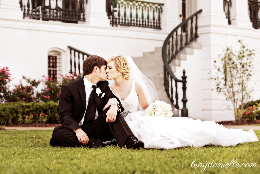 bride and groom sitting on the ground and kissing