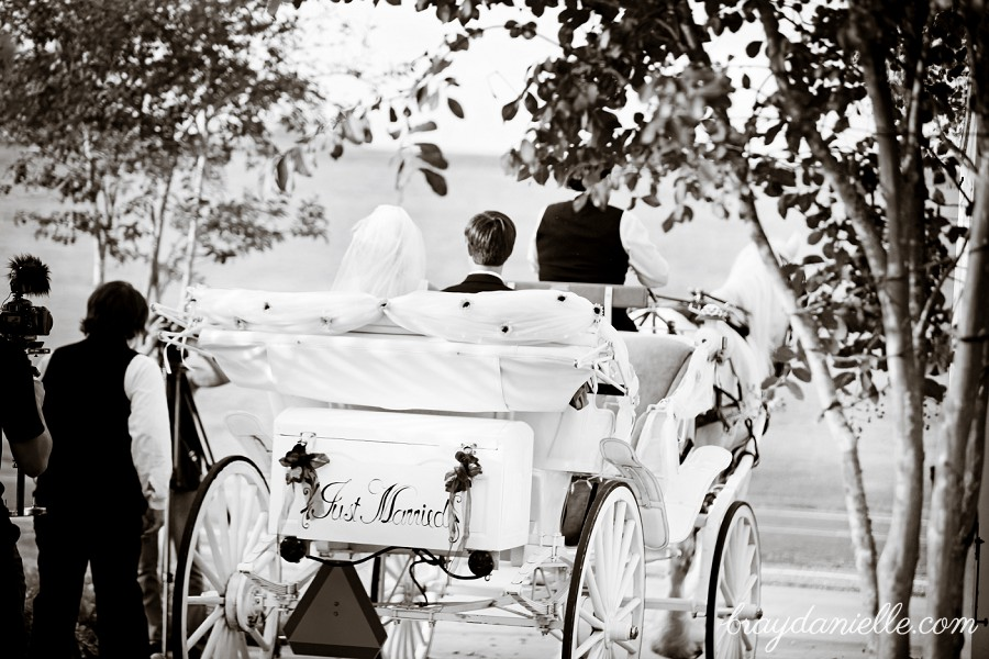 bride and groom riding away in carriage
