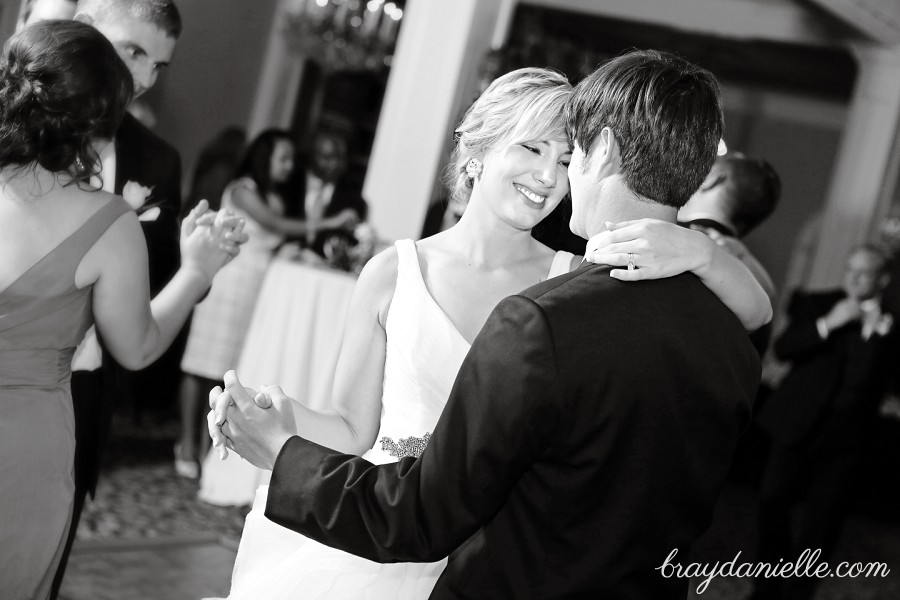 bride smiling at groom while dancing