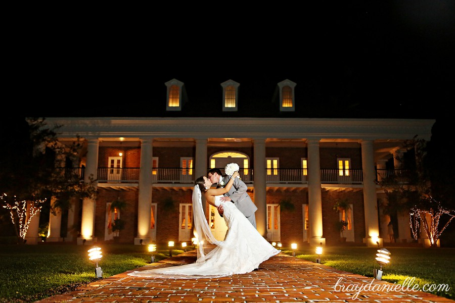 Bride And Groom Kissing In Front Of White Oak Plantation At Night
