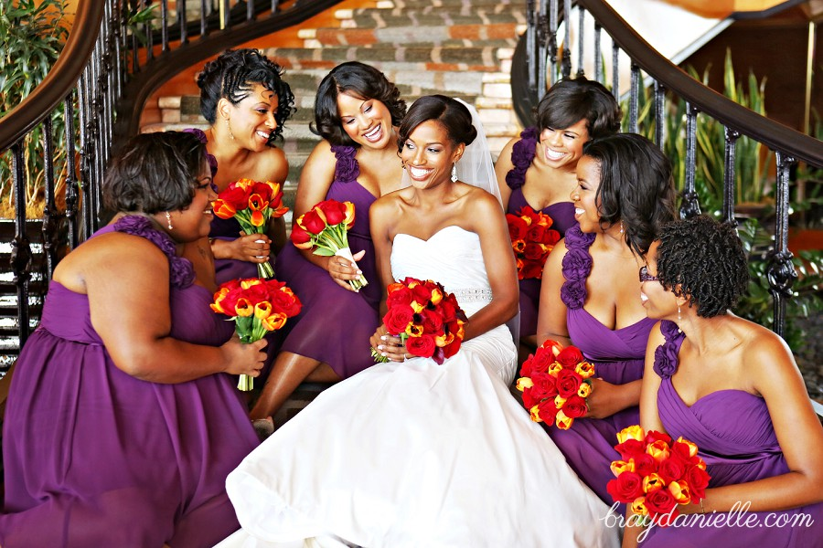 Bridal party posed on steps smiling at the bride purple dresses