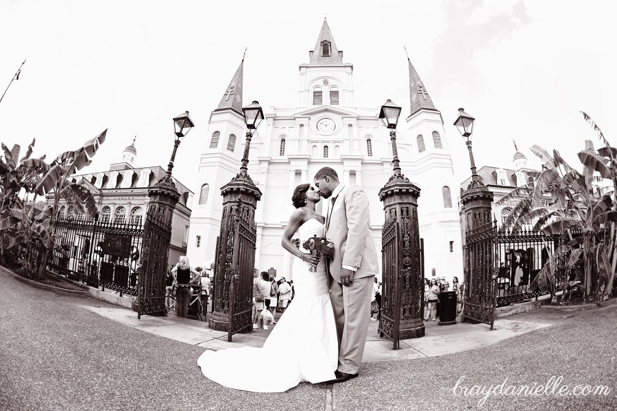 bride and groom kissing in front of cathedral