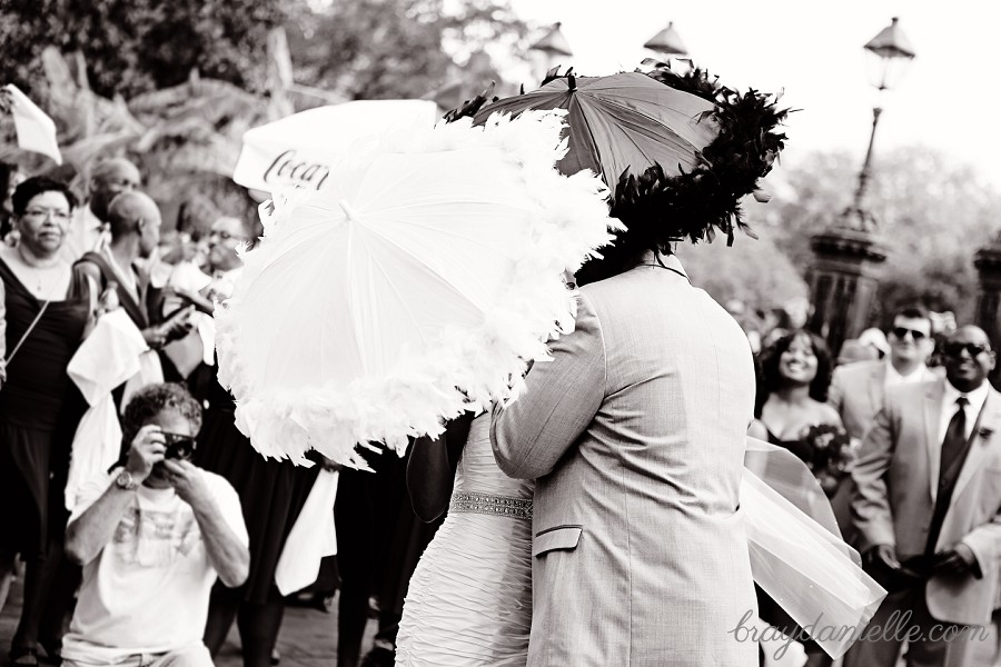 Bride and groom kissing behind parosels