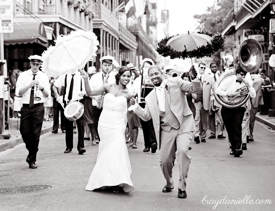 Bride and groom walking down the street with jazz band