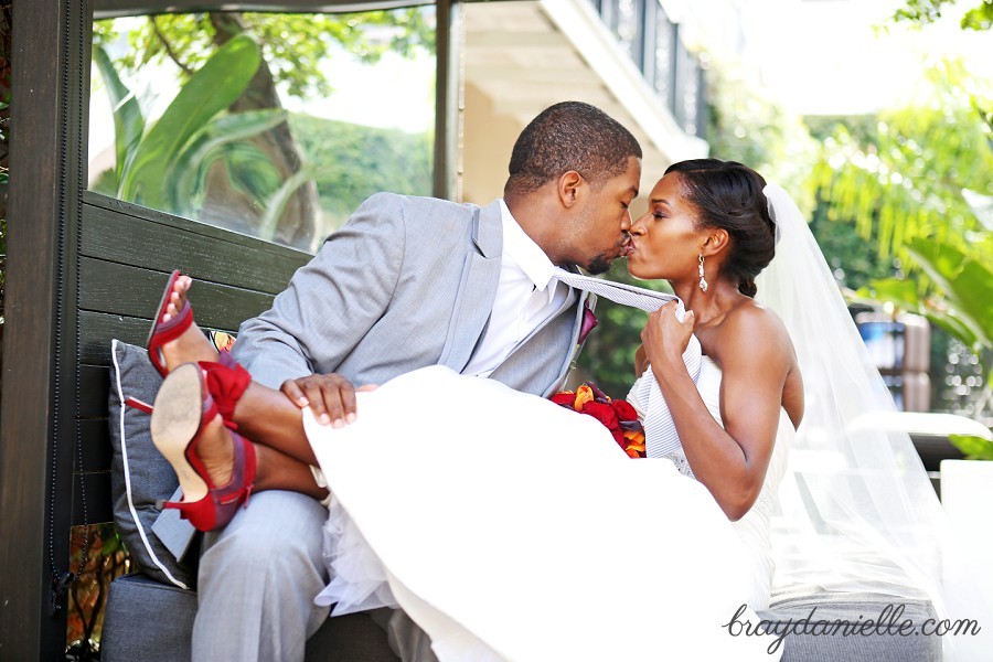 bride pulling the grooms tie while kissing