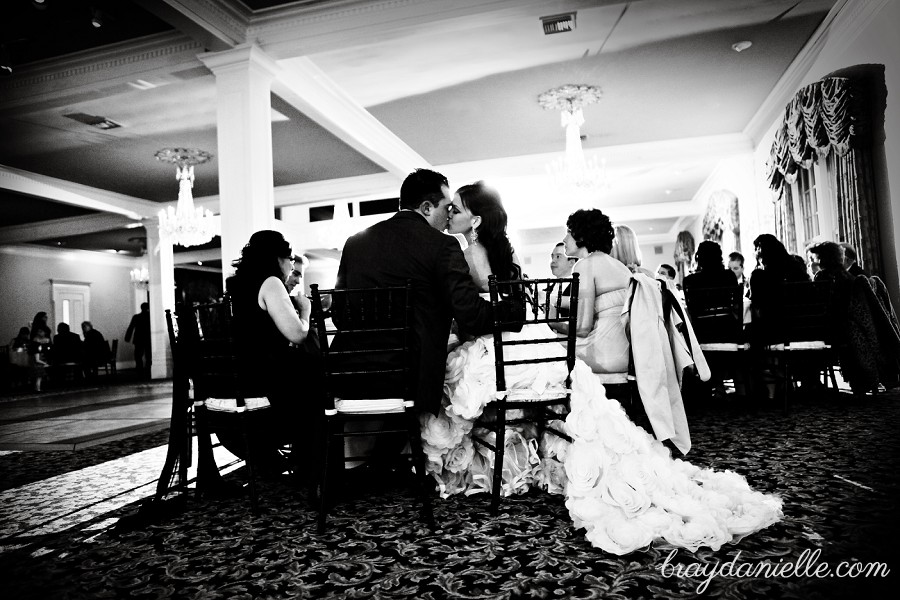 bride and groom kissing while seated